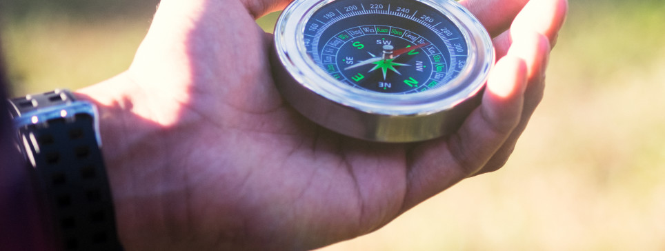 Hiker searching direction with a compass in the forest. View of hands. Point of view shot. Space for text in right left of image